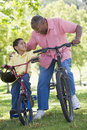 Grandfather and grandson on bikes outdoors smiling Stock Photo