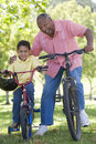 Grandfather and grandson on bikes outdoors smiling Stock Image