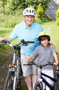 Grandfather and grandson on cycle ride in countryside smiling to camera Royalty Free Stock Photography