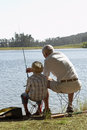 Grandfather and grandson fishing by lake rear view of Stock Image