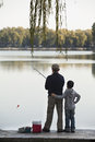 Grandfather and grandson fishing off of dock at lake Royalty Free Stock Photo