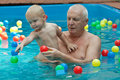 Grandfather and grandson having fun in the pool. Stock Photography