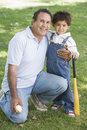 Grandfather and grandson holding baseball bat Royalty Free Stock Photography