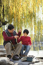 Grandfather and grandson putting lure on fishing line Royalty Free Stock Image