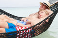 Grandfather and grandson relaxing in beach hammock asleep Stock Photos