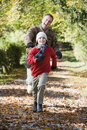 Grandfather and grandson running through woods Royalty Free Stock Photography