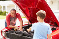 Grandfather and grandson working on restored classic car Stock Photo