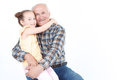 Grandfather with his grand daughter portrait of a pretty small girl wearing yellow top smiling and sitting on the knees of her Royalty Free Stock Photography