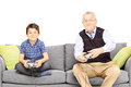 Grandfather with his nephew seated on a modern sofa playing vide video games isolated white background Royalty Free Stock Images