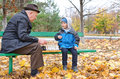 Grandfather playing chess with his little boy sitting back on a park bench Stock Photography