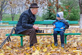 Grandfather playing chess with his little boy sitting back on a park bench Royalty Free Stock Photos