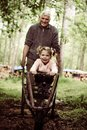 Grandfather pulls little girl on hand cart. Royalty Free Stock Photo
