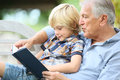 Grandfather reading story to his grandchild book with grandson Stock Photo