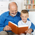 Grandfather reading to his grandson small who is looking up smile at the camera Royalty Free Stock Photo