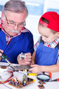 Grandfather showing pcb soldering to grandchild shallow dof only the old men in focus Royalty Free Stock Photos