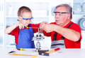 Grandfather teaching grandchild rasping metal in workshop Stock Images