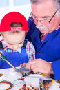 Grandfather teaching grandchild soldering with iron of pcb Royalty Free Stock Photos