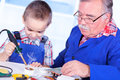 Grandfather teaching grandchild to use soldering resin how when Royalty Free Stock Images