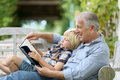 Grandfather telling story to his grandson reading book with Royalty Free Stock Images