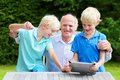 Grandkids teaching grandpa to use tablet pc two happy siblings twin teenage brothers spending time together with grandfather him Stock Photography