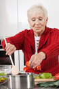 Grandma cooking active elder person preparing lunch for family Stock Image