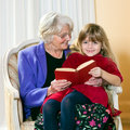 Grandma reading to her grand daughter as she sits on lap Stock Photos