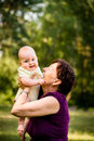 Grandmother with baby grandchild senior women holding her granddaughter outdoor in nature Stock Photos