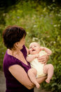 Grandmother with baby grandchild senior women holding her granddaughter outdoor in nature Stock Images