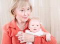 Grandmother with baby on hands at home elegant young granny having fun grandchild happy family generation new life concept Royalty Free Stock Images