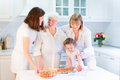 Grandmother baking an apple pie with her family daughter granddaughter and great grand daughter a cute toddler girl in a sunny Stock Image