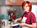 A grandmother beats eggs Royalty Free Stock Photo