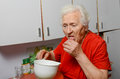 Grandmother drinking pill she is wearing a red jacket Stock Photography
