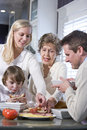 Grandmother with family eating lunch in kitchen Royalty Free Stock Photos