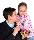 Grandmother feeds strawberry pie to her granddaughter on a white background Royalty Free Stock Photos