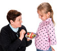 Grandmother feeds strawberry to her granddaughter pie on a white background Royalty Free Stock Images