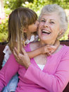 Grandmother getting a kiss from granddaughter Stock Photos