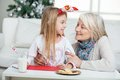 Grandmother and girl with cardpaper looking at happy each other during christmas home Royalty Free Stock Images