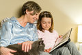 Grandmother and girl looking at photo album petting a cat Royalty Free Stock Photography