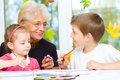 Grandmother with grandchildren painting paintbrush and colorful paints autumn background Royalty Free Stock Photos