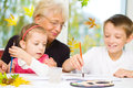 Grandmother with grandchildren painting paintbrush and colorful paints autumn background Stock Photo