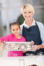 Grandmother granddaughter cookies and holding tray of homemade to be baked Stock Photography