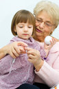 Grandmother with granddaughter cute little girl and her knitting together Stock Images