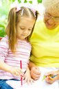 Grandmother with granddaughter drawing little girl her using crayons outdoors Stock Images