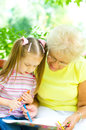 Grandmother with granddaughter drawing little girl her using crayons outdoors Royalty Free Stock Images