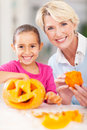 Grandmother granddaughter halloween pumpkin cheerful and her making at home Royalty Free Stock Photography