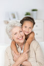 Grandmother and granddaughter happy smiling affectionate her cute little giving each other a loving hug as they smile at the Royalty Free Stock Photo