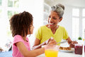 Grandmother and granddaughter having breakfast together in kitchen whilst smiling at each other Stock Photography