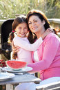 Grandmother and granddaughter having outdoor barbeque smiling to camera Royalty Free Stock Photo