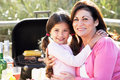 Grandmother and granddaughter having outdoor barbeque smiling to camera Royalty Free Stock Photos