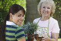 Grandmother And Granddaughter Holding Potted Plants Stock Images